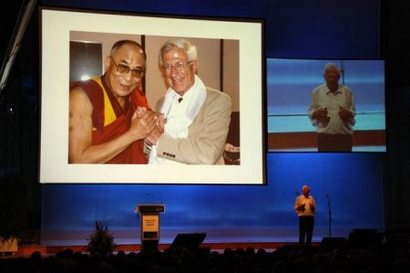 Der Journalist Dr. Franz Alt bei seinem Plenumsvortrag auf dem Heiligenfelder Kongress. Im Hintergrund ist er mit dem Friedensnobelpreisträger Dalai Lama zu sehen. Beide verbindet eine langjährige Freundschaft. Foto: Kai Fraass